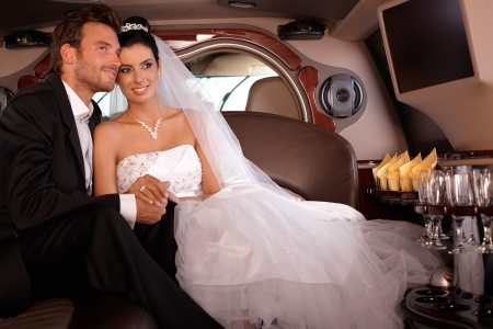 Bride and groom sitting in limousine, smiling happily. photo