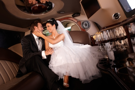 limo: Happy couple embracing in limousine on wedding-day.