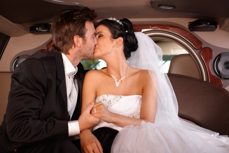 Bride and groom kissing in limousine on wedding-day. photo