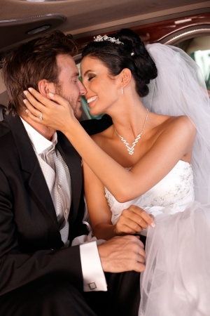 beautiful bride: Bride and groom kissing in limousine, embracing.