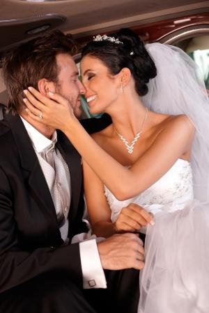 be kissed: Sposa e sposo in limousine baciare, abbracciare. Archivio Fotografico