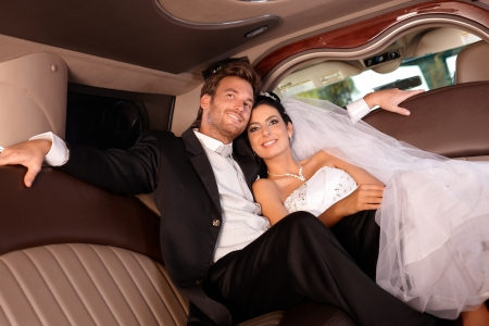 limo: Beautiful young couple smiling happily on wedding-day, sitting in limousine.