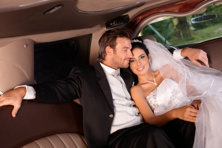 Happy couple sitting in limousine on wedding-day. Stock Photo