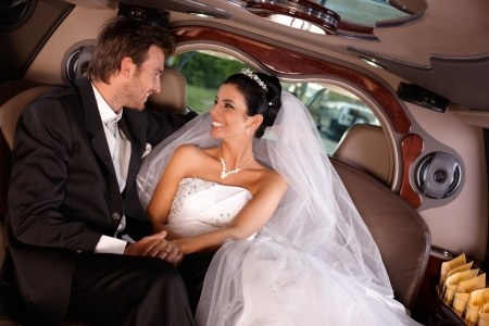 wedding gown: Happy young couple sitting in limousine on wedding day.