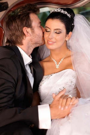be kissed: Groom kissing bride fondly on wedding-day. Stock Photo