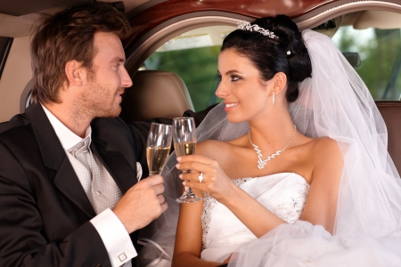beautiful marriage: Bride and groom sitting in limousine, clinking glasses on wedding-day.