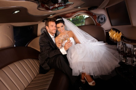 Romantic young couple sitting in limo on wedding-day, clinking glasses. photo