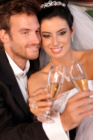 groom and bride: Beautiful engaged couple smiling on wedding-day, clinking glasses.