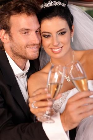 Beautiful engaged couple smiling on wedding-day, clinking glasses. photo