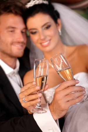 clinking: Bride and groom clinking glasses on wedding-day. Focus on champagne flutes.