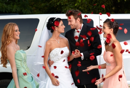 wedding gown: Bridesmaids throwing rose petals on young couple. Stock Photo