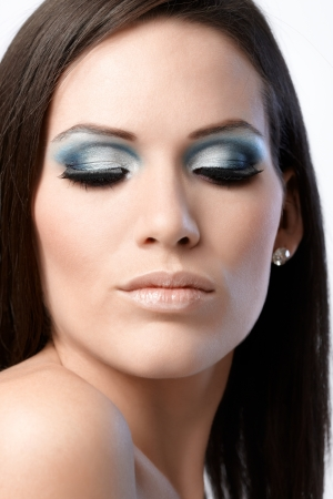 Beauty portrait of attractive woman in makeup, looking down. Stress on blue eyelids and long lashes. photo