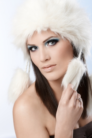 Winter beauty in fur cap and makeup, looking at camera. photo