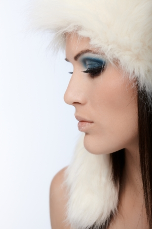 Profile of winter beauty in white fur hat and fancy makeup. photo