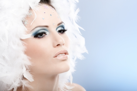 Beautiful young model with professional winter makeup and white feather cap. photo