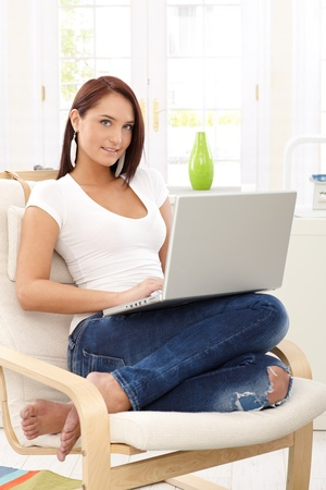 Lachende mooie vrouw zittend in fauteuil met laptop computer in lichte woonkamer.