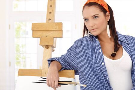Attractive visual artist posing at painting canvas with brush. photo