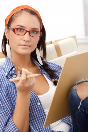 drawing pad: Attractive girl wearing glasses with colorful pencil and drawing pad, looking at camera. Stock Photo