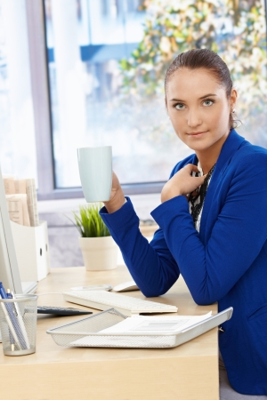 Portrait of pretty office assistant girl sitting at desk on coffee break, holding mug. Stock Photo - 14767421