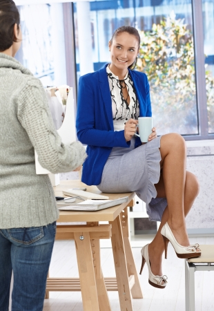 break in: Portrait of relaxing pretty businesswoman in fancy skirt and high heels sitting on desk in office chatting to colleague while on coffee break.