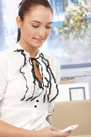 business woman phone: Young smiling businesswoman in fancy shirt texting on mobile phone in office, looking down.