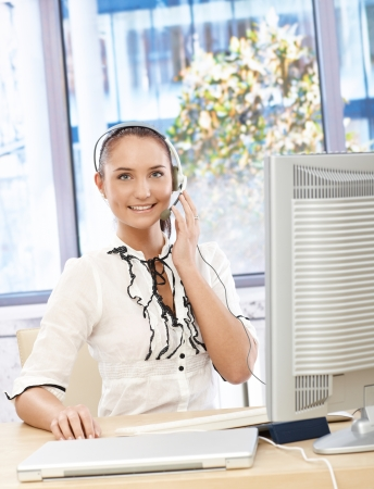 Happy office girl speaking on headset, smiling, using desktop computer in customer service office. photo