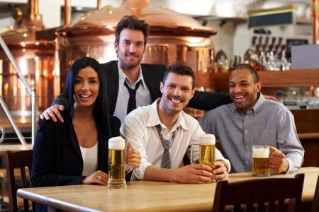 hombre tomando cerveza: Grupo de amigos felices j�venes bebiendo cerveza en el pub, sonriendo. Foto de archivo