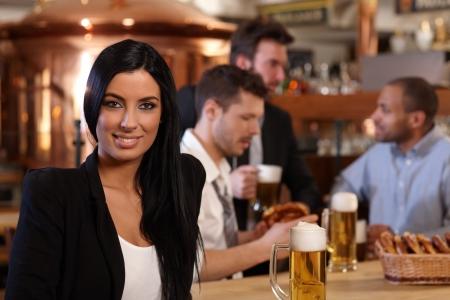 Beautiful young woman sitting at bar, drinking beer. Looking at camera, smiling.