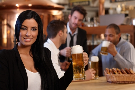 horizontal bar: Portrait of beautiful young woman holding mug of beer in pub, looking at camera, smiling. Friends drinking in background.