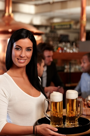 Beautiful young waitress in pub, holding beer mugs on tray, smiling. photo