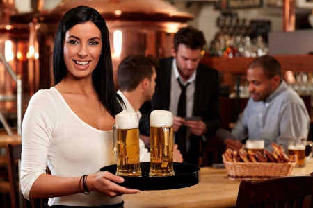 serving tray: Portrait of happy young woman serving beer in bar, looking at camera smiling.
