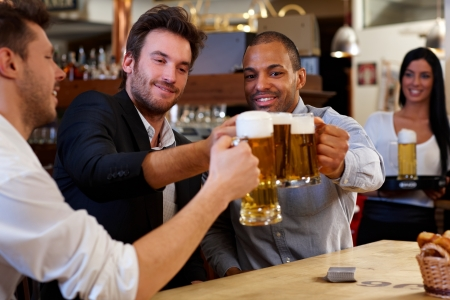 social drinking: Happy friends clinking with beer mugs in pub, smiling. Stock Photo
