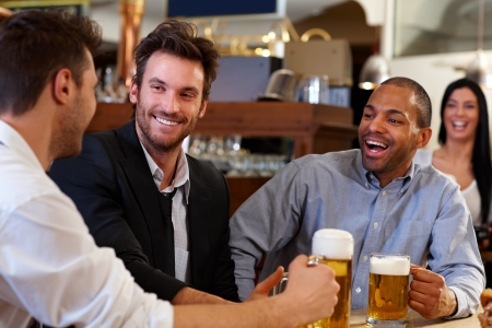 horizontal bar: Happy young businessmen drinking beer and talking at pub after work. Looking at each other smiling. Stock Photo