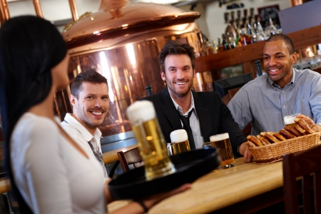 Happy young men sitting at table in pub in pub looking at waitress holding beer, smiling. photo