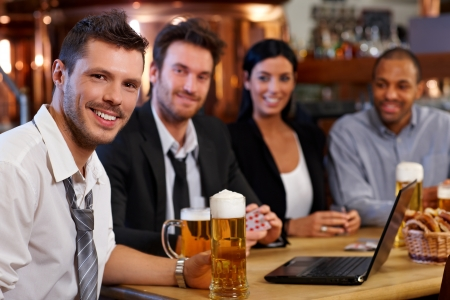 Happy young office worker drinking beer at pub with colleagues, holding mug, smiling. photo