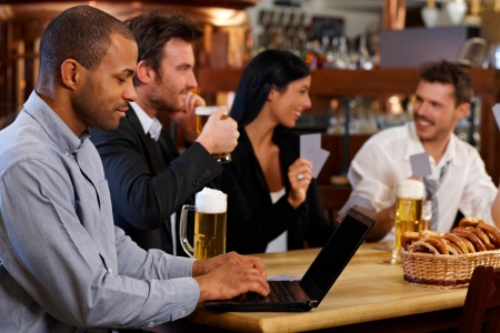 horizontal bar: Young man browsing internet using laptop in pub, looking at screen. Friends drinking beer at background.