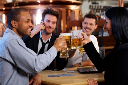 horizontal bar: Group of happy young office workers clinking with beer at pub, looking at each other, smiling.