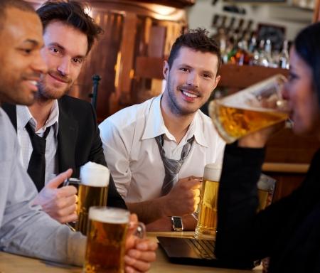 socializando: Grupo de gente joven en pub. Chica bebiendo cerveza taza de otros están mirando y sonriendo.