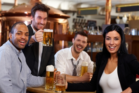 mate drink: Happy friends having fun in pub watching sport in TV together drinking beer cheering for team. Stock Photo