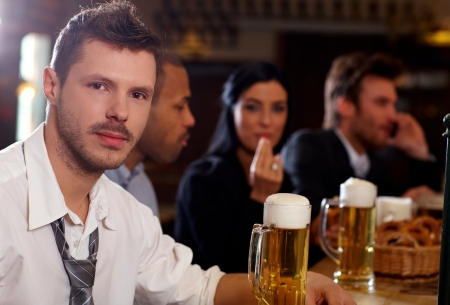 Portrait of casual young businessman drinking beer in pub, looking at camera. photo