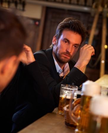 hombre tomando cerveza: Retrato de hombre de negocios joven que bebe demasiada cerveza en el pub, mirando confundido.