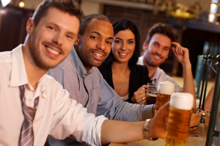 horizontal bar: Portrait of happy young people sitting in pub, drinking beer, looking at camera, smiling.