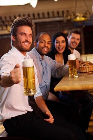 socializando: Potable feliz joven con sus amigos en pub. Sosteniendo la taza de cerveza, mirando a cámara, sonriendo.