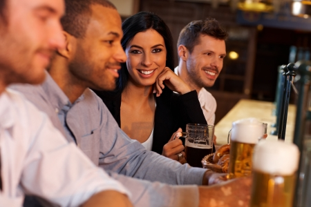 horizontal bar: Beautiful young woman sitting at pub with friends, drinking beer. Looking at camera, smiling.