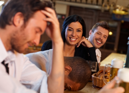 Beautiful young woman having fun with friends in pub. Looking at camera, laughing. photo