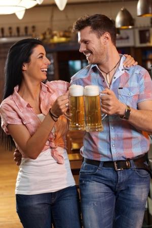clinking: Feliz pareja joven que tintinean con la cerveza en el pub, mirando el uno al otro sonriendo. Foto de archivo