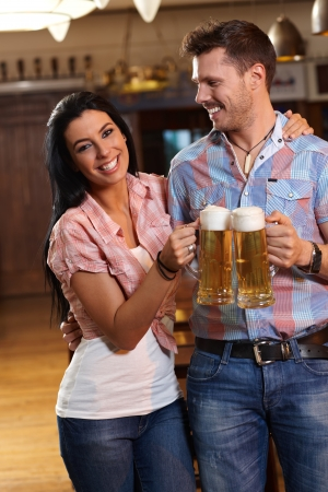 hombre tomando cerveza: Feliz joven bebiendo cerveza en pareja pub, copas tintineantes, sonriendo. Foto de archivo