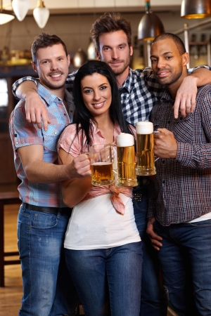 Group of happy young friends drinking beer at pub, smiling, clinking glasses photo