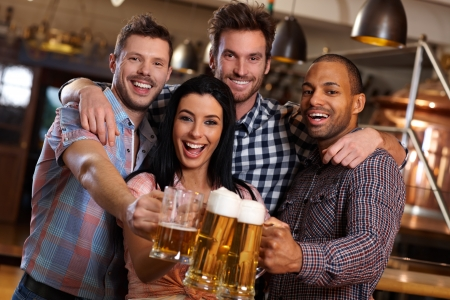 cheers: Group of happy young friends drinking beer at pub, laughing, clinking glasses