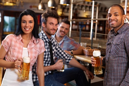 socializing: Happy young people drinking beer in pub, smiling.